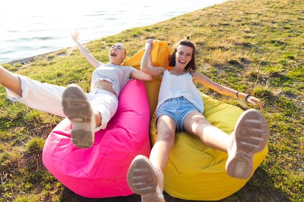 Ragazze della possibilità remota che si siedono sui beanbags
