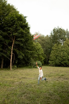 Long shot of happy boy having fun with a kite