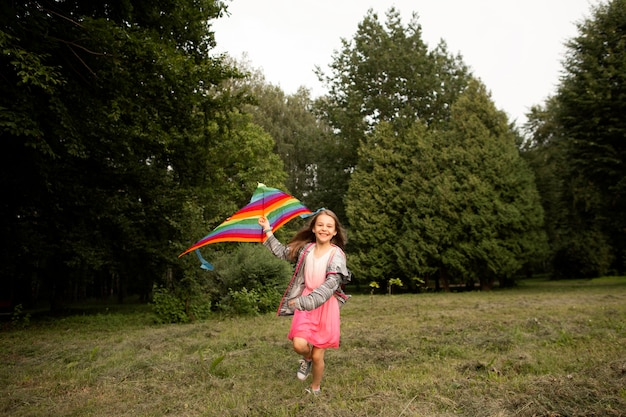 Long shot of happy girl having fun with a kite