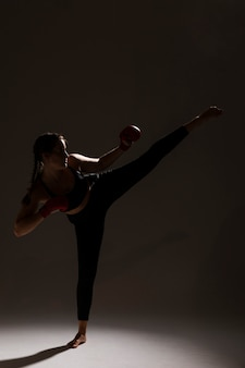 Long shot of karate woman dark background
