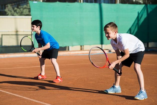 Long shot kids playing double tennis
