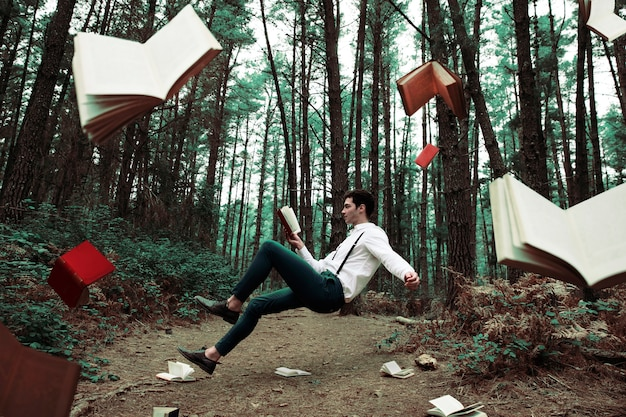 Long shot levitating man reading in the forest