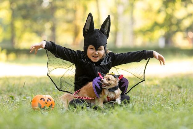 Long shot of little boy in bat costume