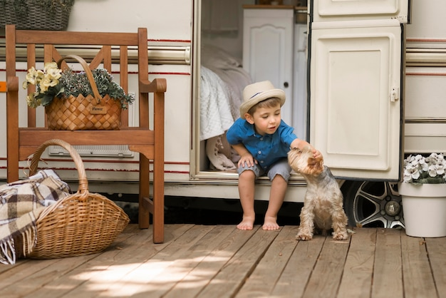 Long shot little boy sitting on a caravan next to a cute dog