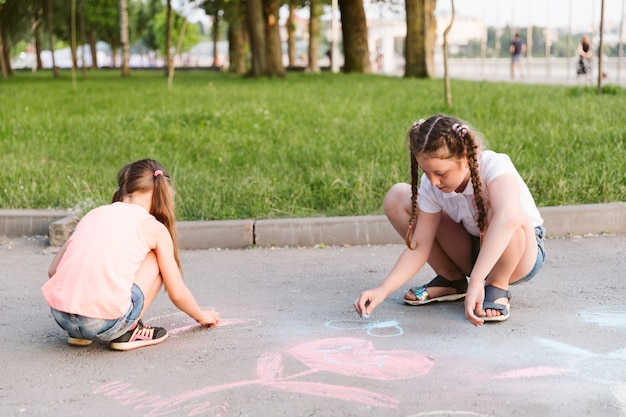 Long shot little girls drawing with chalk