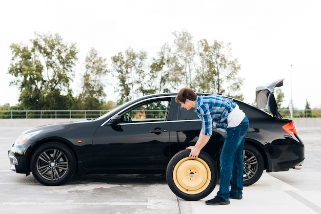 Long shot of man changing tire