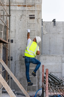 Long shot man climbing the stairs on a construction site