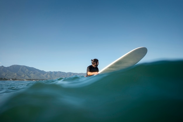 Colpo lungo dell'uomo sulla sua tavola da surf