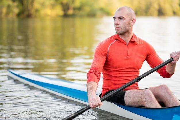 Long shot man holding oar