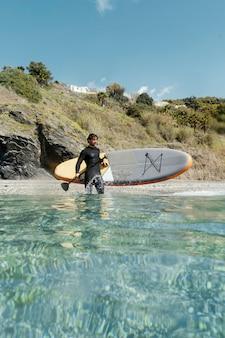 Длинный выстрел человек, держащий доску для серфинга