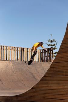 Человек с длинным выстрелом прыгает на скейтборде