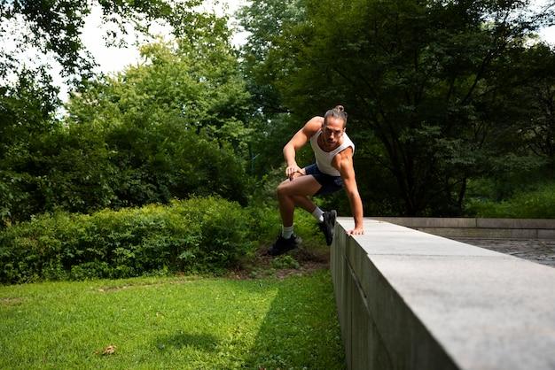Colpo lungo dell'uomo che salta sopra il recinto di pietra