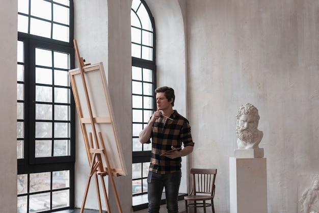 Long shot man looking at painting on canvas