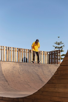 Человек с длинным выстрелом на скейтборде