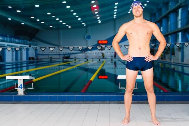 Long-shot man posing in front of swimming pool