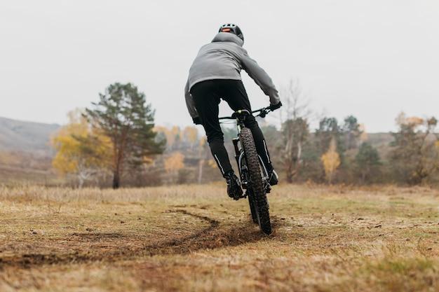 Colpo lungo dell'uomo che guida una bicicletta