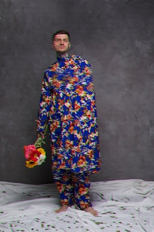 Long shot of man in robe holding flowers