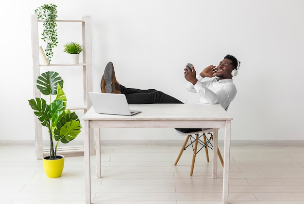 Long shot of man sitting at the desk and listening to music