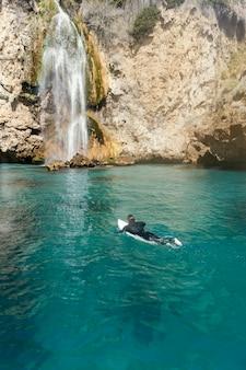 Человек с длинным выстрелом плавает с доской для серфинга