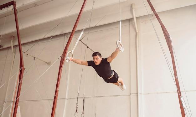 Человек с длинным выстрелом тренируется на гимнастических кольцах
