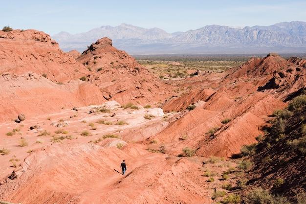 Long shot man walking in canyon landscape