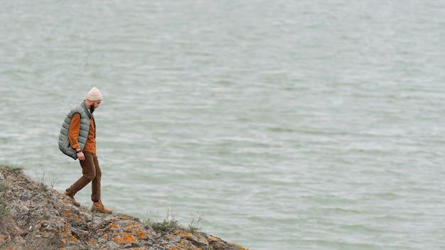 水に向かって歩くロングショットの男