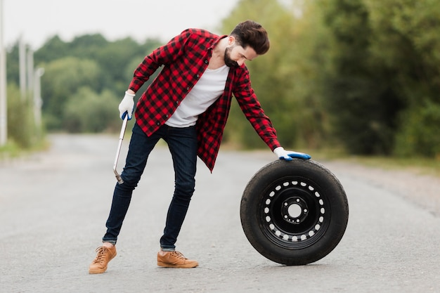 Long shot of man with wrench and tire
