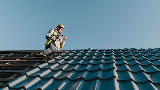 屋根に取り組んでいるロングショットの男