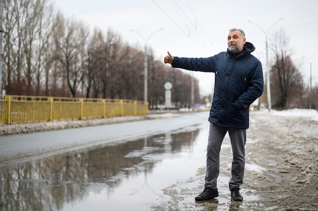 Long shot mature man waiting for a car
