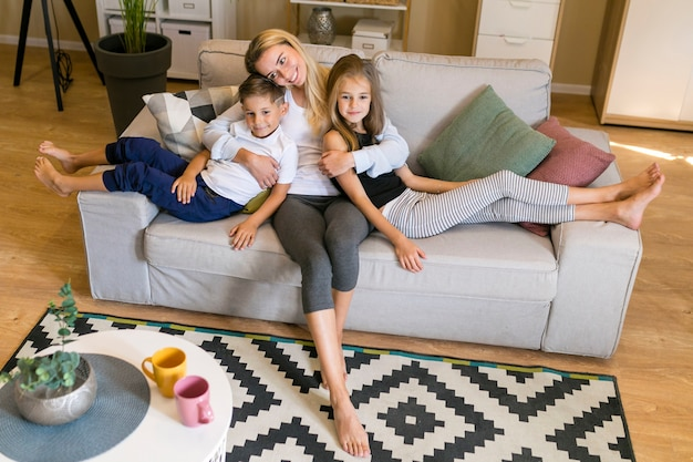 Long shot of mother and children sitting on a couch