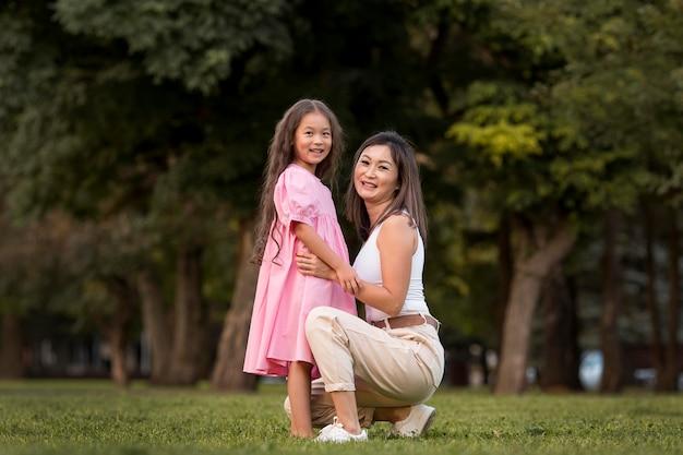 娘を屋外で抱きしめるロングショットの母親
