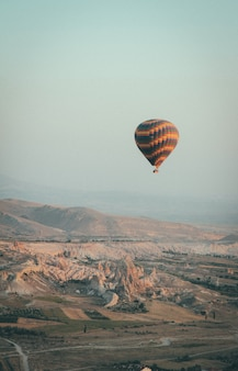 Long shot of a multi-colored hot air balloon floating in the sky high above mountains