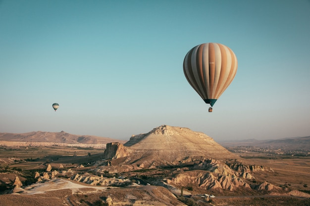 Long shot of multi-colored hot air balloons floating above the mountains