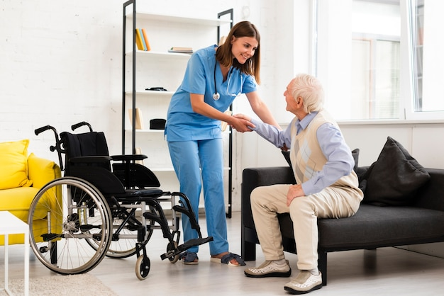 Long shot nurse helping old man getting up