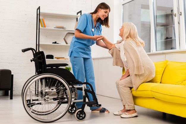 Long shot nurse helping old woman getting up