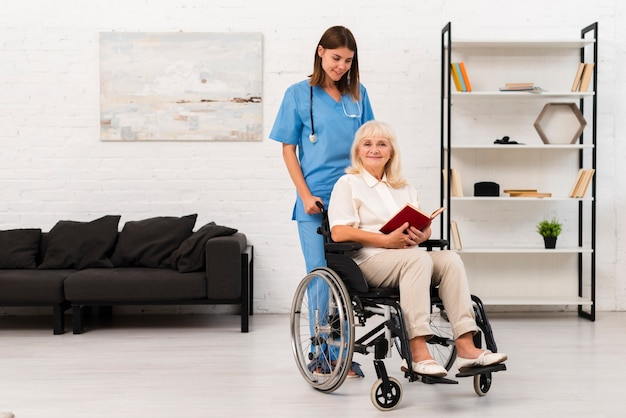 Long shot nurse taking care of woman in wheelchair
