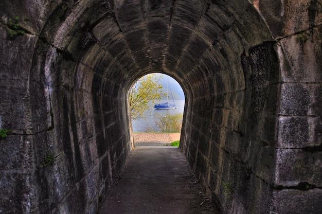 反対側にボートがある湖の景色を望むアーチ型のレンガのトンネルのロングショット