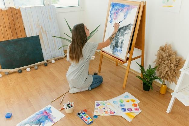 キャンバス上のアーティストの抽象絵画のロングショット