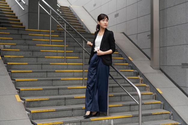 階段の上の美しいビジネス女性のロングショット