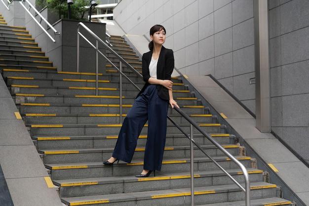 계단에 아름 다운 비즈니스 우먼의 긴 총