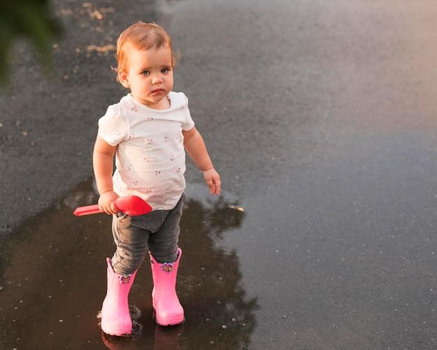 Снимок красивого ребенка, играющего на улице