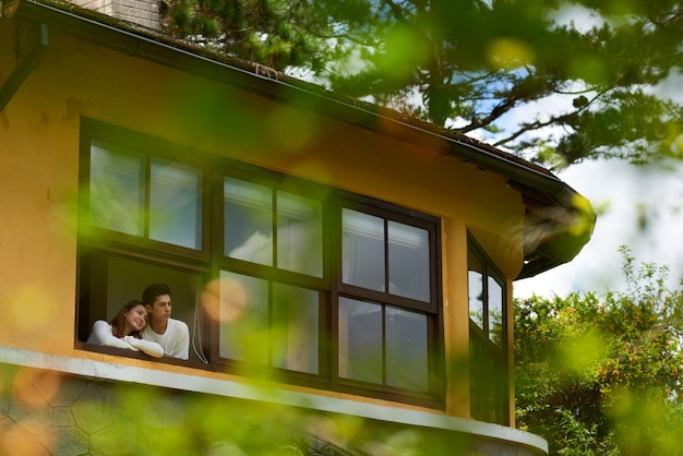 彼らの新しい家の窓の外を見ているカップルのロングショット