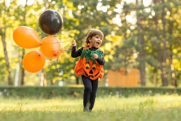 Длинный снимок милого маленького мальчика в костюме тыквы