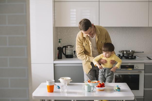 Длинный выстрел отца, держащего его сына на кухне