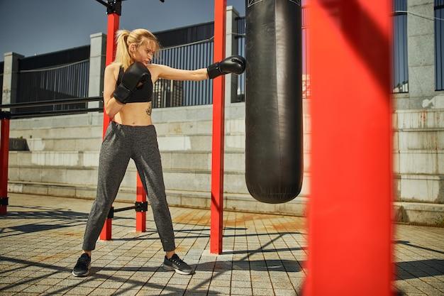 スポーツグラウンドでのキックボクシングトレーニング中にボクシンググローブで左手でパンチを見せているフィット女性のロングショット
