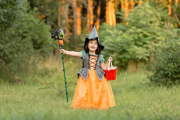 自然の中で魔女のハロウィーンの衣装を持つ少女のロングショット