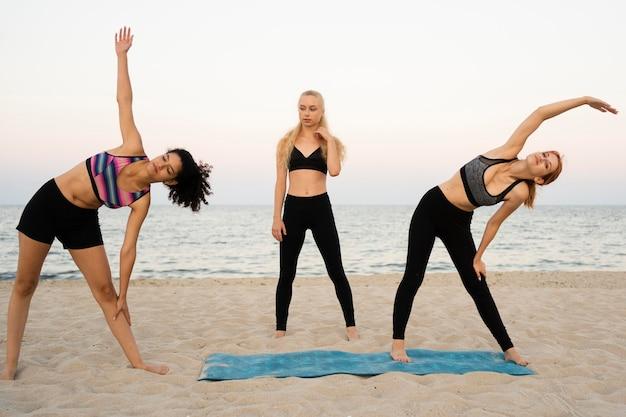 Длинный снимок девушек, тренирующихся на пляже