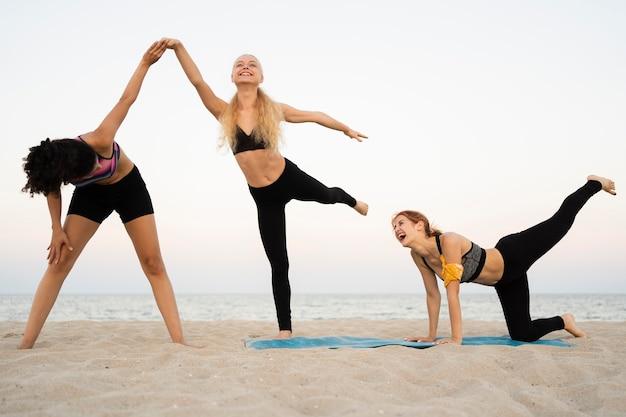 ビーチで運動している女の子のロングショット