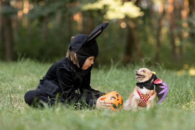 コウモリの衣装と犬の少年のロングショット