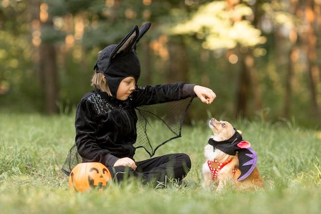 Длинный снимок маленького мальчика в костюме летучей мыши и собаки